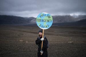 Dievča drží transparent počas výstupu na vulkán Ok  počas výstupu na miesto, kde sa kedysi nachádzal ľadovec Okjökull.