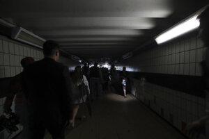 Ľudia kráčajú v tme cez londýnsku stanicu Clapham Junction počas výpadku 9. augusta 2019.