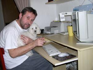 Rasťo Piško doma pri práci so svojím psíkom Pigim.