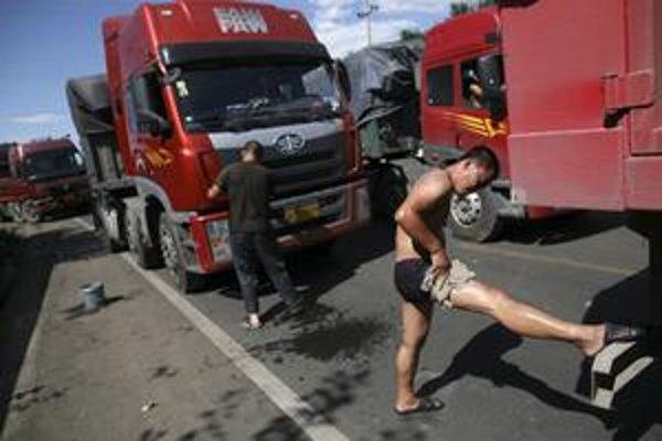 Kamionista sa umýva po tom, čo viac ako dva dni čaká v dopravnej zápche na vstupnej bráne na diaľnicu spájajúcu Peking s Tibetom.