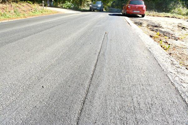 Poškodená cesta po pokládke prvej vrstvy asfaltu.