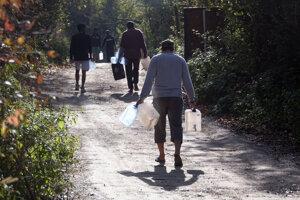 Migranti nesú prázdne kanistre na vodu pri utečeneckom tábore Vucjak 21. októbra 2019.