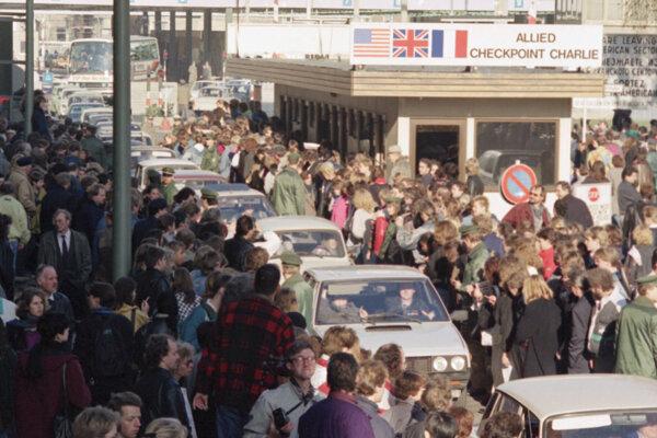 Autá z východného Berlína prechádzajú cez Checkpoint Charlie.
