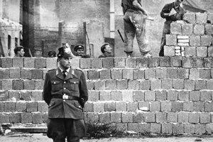 Na archívnej snímke zo 7. októbra 1961 berlínsky policajt stráži robotníkov pri stavbe múru.