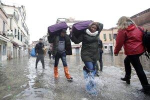 Turisti s batožinou sa brodia v zaplavenej ulici v Benátkach.