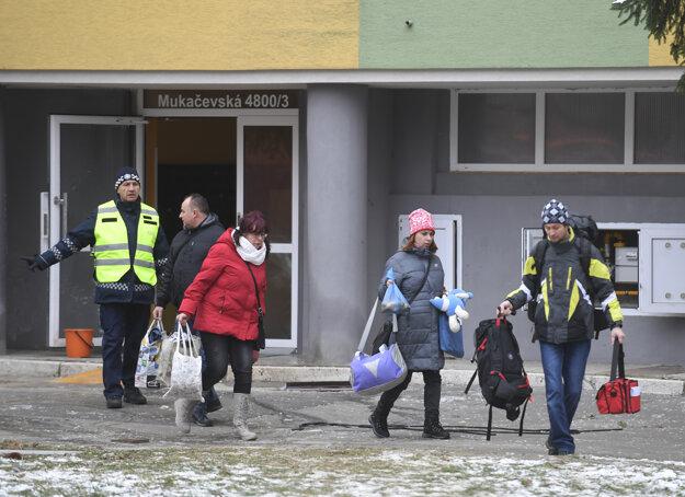 Ľudia si za asistencie polície odnášajú základné veci z evakuovaného vedľajšieho paneláku na Mukačevskej 3 v Prešove.