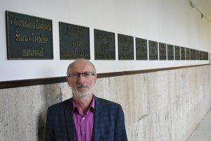 Riaditeľ školy Pavol Kováč pred 18 tabuľkami vybraných absolventov.