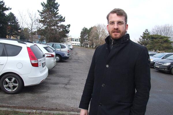 Martin Hodál na parkovisku, ktoré chcú zastavať. Vzadu je zápasnícka hala, vpravo rieka.