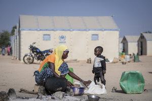 Žena s dieťaťom pripravuje jedlo v tábore Pissila. Kaya, Burkina Faso, 10. december 2019.