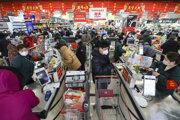 Ľudia s rúškami na tvári v čínskom Wu-chane si robia zásoby. Pre šíriaci sa vírus väčšina zostáva doma.