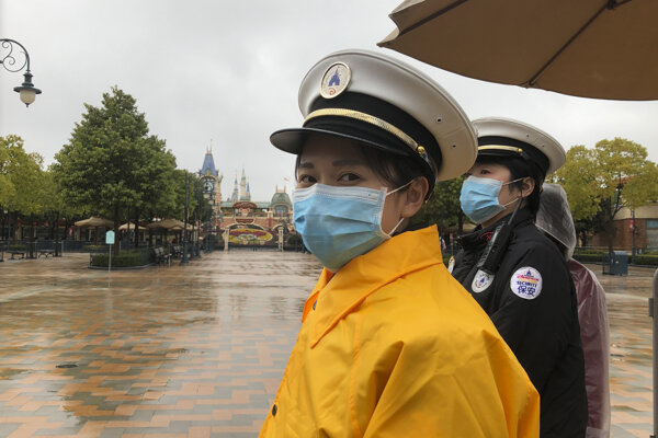 Zamestnanci bezpečnosti pred zatvoreným Disneylandom v Šanghaji.