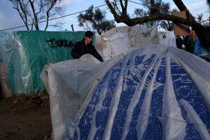 Migrant prikrýva stan plastovou fóliou. Lesbos, Grécko 28. január 2020.