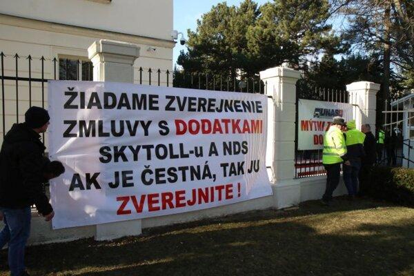 Transparenty na plote Úradu vlády SR počas protestného zhromaždenia Únie autodopravcov Slovenska (UNAS) za otvorenie zmluvy a dodatkov na mýtnom systéme a vyvodenia trestnoprávnej zodpovednosti na generálnej prokuratúre.