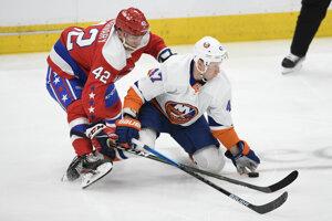 Obranca Washingtonu Martin Fehérváry (vľavo) v súboji s útočníkom Leom Komarovom z New York Islanders.