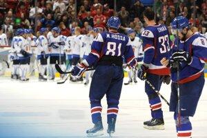 Sklamaní slovenskí hokejisti sledujú fínsku radosť.