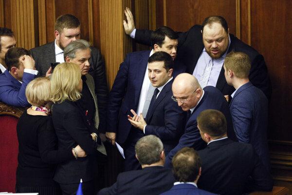 Ukrajinský prezident Volodymyr Zelenskyj (uprostred) diskutuje s poslancami na zasadnutí parlamentu v Kyjeve.