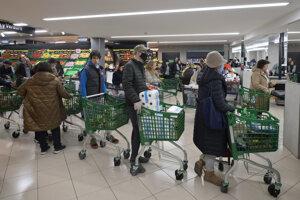 Zákazníci, niektorí s ochrannými rúškami, čakajú pri pokladniciach v supermarkete v španielskom Madride.