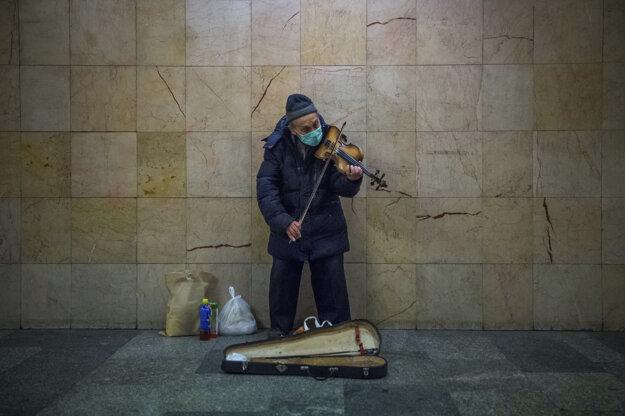 Pouličný muzikant s ochranným rúškom hrá na violu na stanici metra Nyugati Pályaudvar počas núdzového stavu spôsobeného pandémiou koronavírusu v Budapešti v Maďarsku.