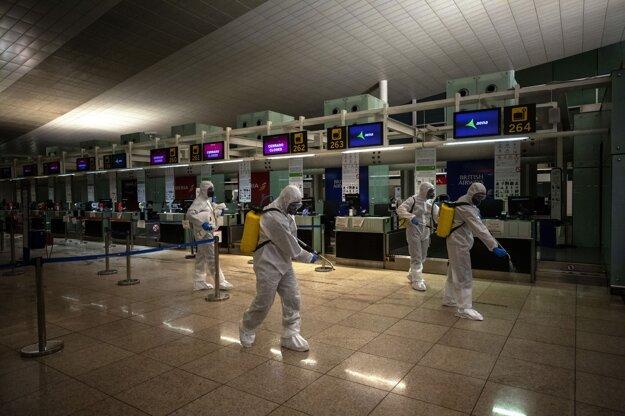 Príslušníci španielskej vojenskej jednotky UME pri dezinfekcii leteckého terminálu proti koronavírusu COVID-19 na letisku v Barcelone v Španielsku.