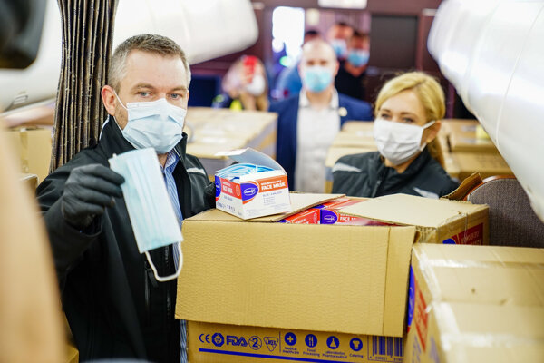 Už bývalý premiér Peter Pellegrini a bývalá ministerka vnútra Denisa Saková kontrolujú rúška, ktoré dorazili z Číny.