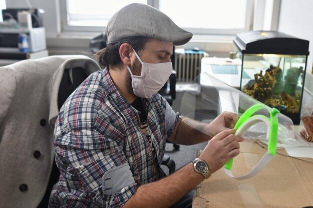 Člen iniciatívy Pomôž nemocnici Robert Jurčo pri skladaní ochranného štítu vyrábaného pre lekárov na 3D tlačiarni.