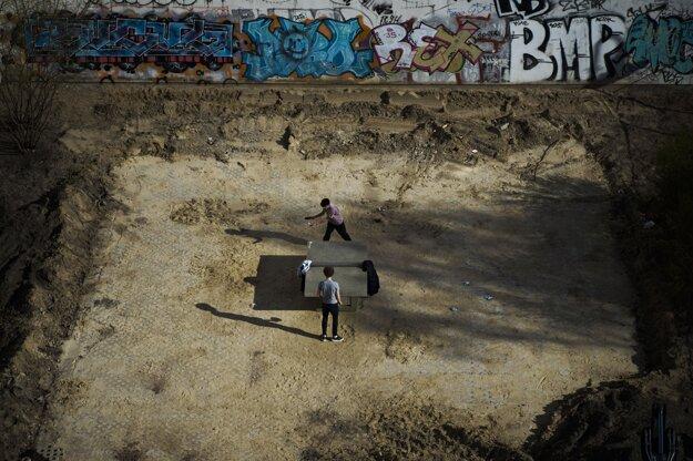 Dvaja muži hrajú stolný tenis na opustenom ihrisku počas slnečného popoludnia v Berlíne.