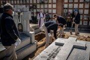 Kňaz a rodina sa modlia na pohrebe obete ochorenia Covid-19 na cintoríne v Madride 28. marca 2020.