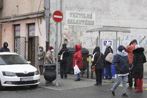 Ľudia čakajú pred textilnou galantériou v Košiciach.
