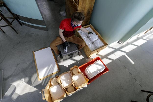 Dobrovoľník pripravuje jedlo na rozvoz.