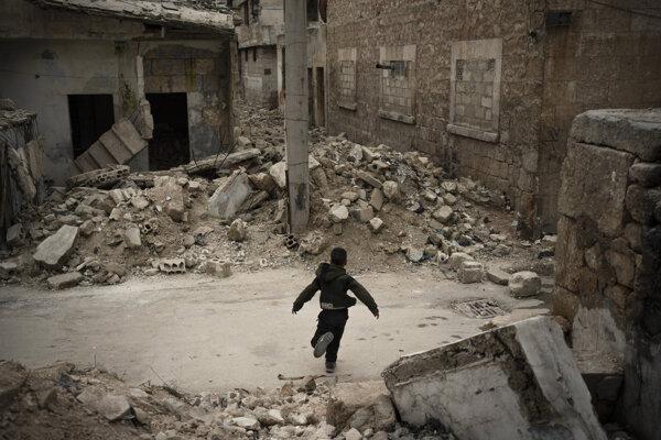 Chlapec sa hrá v troskách zničených budov po náletoch v sýrskom meste Idlib 18. marca 2020