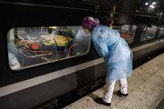Zdravotník sa pozerá na pacienta infikovaného vírusom COVID-19, ktorý leží v rýchlovlaku na vlakovej stanici Gare d'Austerlitz.