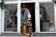 Majiteľ hladká svojho psa, ktorý sa z okna v centre Prahy pozerá von.