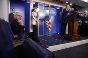Americký prezident Donald Trump (pri rečníckom pulte) na tlačovom briefingu v Bielom dome.  Imunológ Anthony Fauci počúva prezidentov prejav zo sedačky.