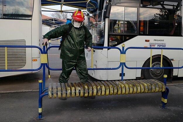 Člen Dobrovoľného hasičského zboru v Kežmarku dezinfikuje špeciálnym prípravkom lavičku na autobusovej stanici v Kežmarku.
