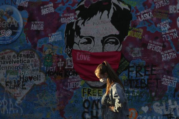 Žena prechádza popri stene Johna Lennona v Prahe.