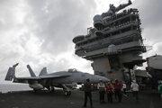 Palubný personál stojí pred bojovým lietadlom F/A-18 Super Hornet amerických námorných síl na lietadlovej lodi USS Ronald Reagan.