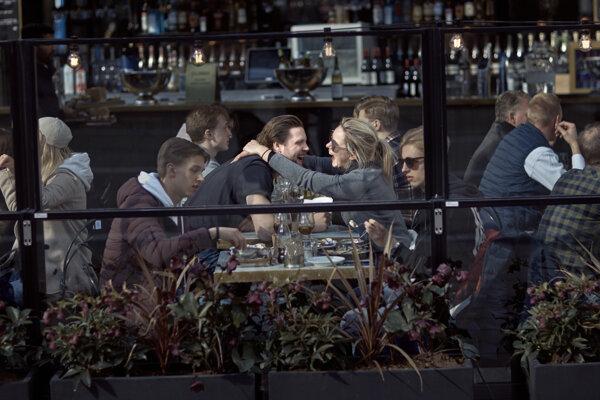 Pár sa usmieva a objíma v plnej reštaurácii v Štokholme v sobotu 4. apríla 2020.