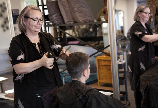 Christel Lercheová strihá zákazníka v kaderníctve v dánskom meste Bagsvaerd 20. apríla 2020.