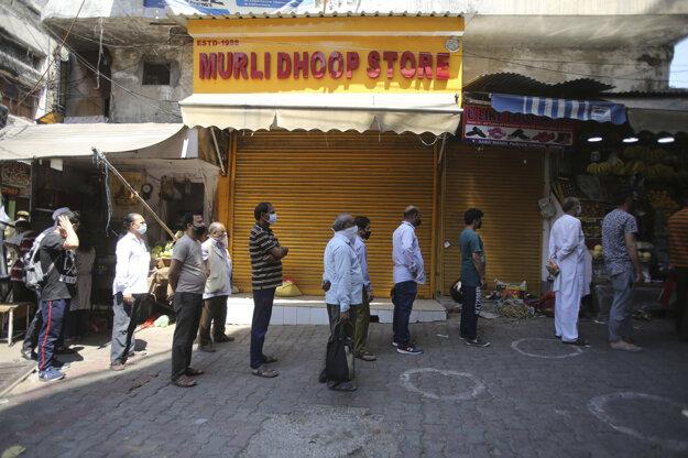 Ľudia stoja v rade pred trhom so zeleninou počas pandémie koronavírusu v Indii.