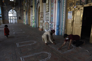 Ľudia označujú miesta v mešite pre veriacich na dodržiavanie sociálneho odstupu počas modlitieb na zabránenie šíreniu nového koronavírusu v pakistanskom meste Rávalpindí.