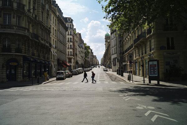 Ľudia kráčajú prázdnou ulicou v Paríži počas obmedzenia pohybu na spomalenie šírenia nového typu koronavírusu.