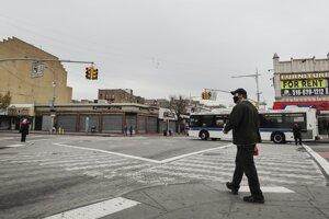 Chodci s ochrannými rúškami na zabránenie šíreniu nového koronavírusu kráčajú po takmer prázdnej ulici Jamaica Avenue v štvrti Queens v New Yorku.