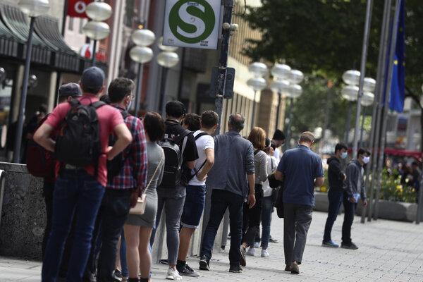 Ľudia čakajú v rade pred obchodom v nemeckom Mníchove.