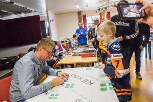 Rastislav Staňa podpisuje kartičku mladému fanúšikovi.