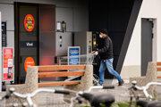 Zákazník s ochranným rúškom na tvári vstupuje do obchodu v slovinskej metropole Ľubľana v utorok 31. marca 2020.