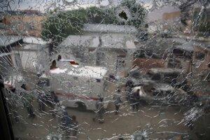 Pohľad na afganských bezpečnostných pracovníkov cez rozbité okno pôrodnice po útoku ozbrojencov v Kábule.