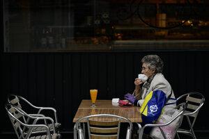 Žena si napráva ochranné rúško na zabránenie šíreniu nového koronavírusu pri sedení na letnej terase miestneho baru v španielskej Pamplone.