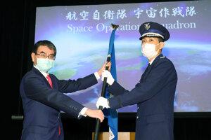 Japonský minister obrany Taro Kono (vľavo) odovzdáva vlajku veliteľovi novej jednotky pre vesmírnu obranu Toshihideovi Ashikimu.