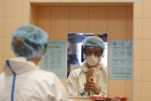 Zdravotná pracovníčka si umýva ruky na jednotke intenzívnej starostlivosti v pražskej univerzinej nemocnici, v ktorej lieča pacientov s ochorením COVID-19.