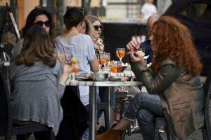 Ľudia sedia vonku pred barom na námestí Campo dei Fiori.